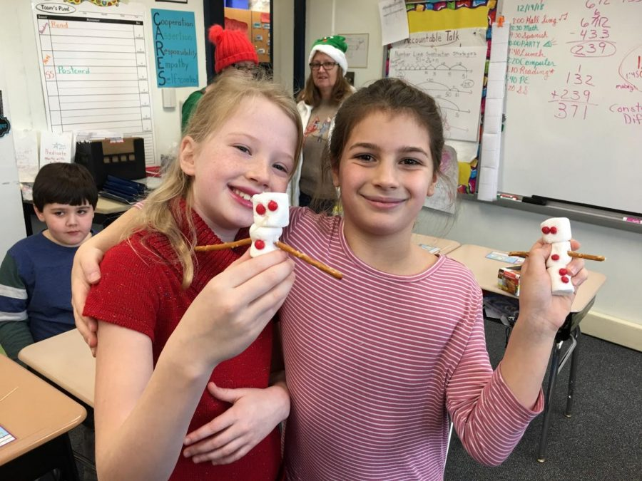 Third graders Juliet Sykes and Mackenzie Wyche enjoy making edible snowmen during the Grade 3 winter holiday celebration. Jayne Parker/Sewickley Academy