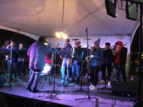"""Sewickley Academy band teacher Mrs. Candreva conducts the Jazz Band as they play holiday tunes on the """"Orr Rock"""" stage in the town of Sewickley. (Eirinin Mahoney/Sewickley Academy)"""
