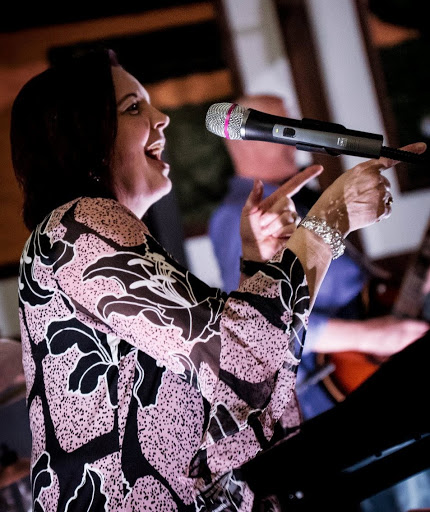 Mrs. Candreva singing at a gig with her band. (Photo by Alex Vu)